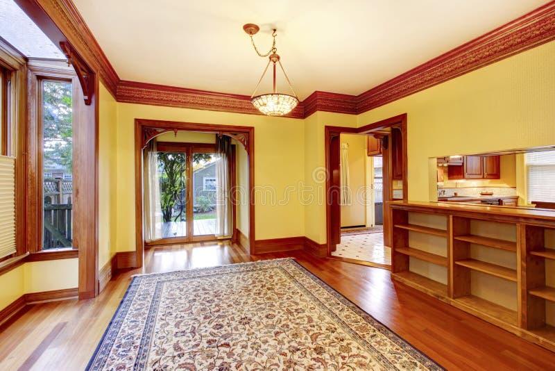 Элегантная пустая живущая комната с желтыми стенами, высекаенный деревянный вход стоковое фото rf