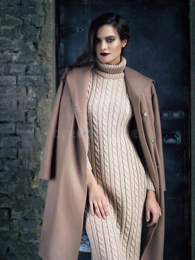 Элегантная фотомодель нося длинное пальто mocha, представляя перед дверью стоковые изображения