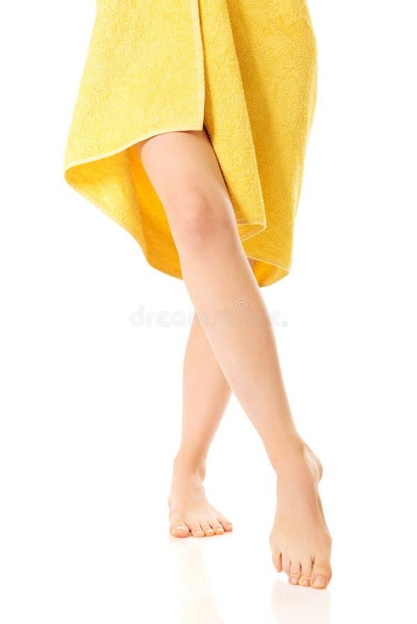 Элегантные женские ноги покрытые с желтым полотенцем стоковые фотографии rf