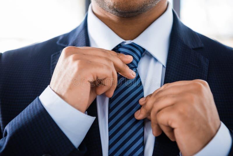 Элегантный бизнесмен в костюме связывая галстук стоковые фотографии rf