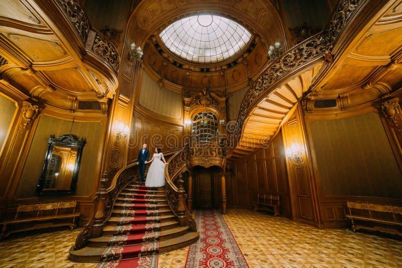 Элегантный жених и невеста шагая - вниз большие деревянные лестницы, представляя в богатом интерьере старого классического особня стоковая фотография rf