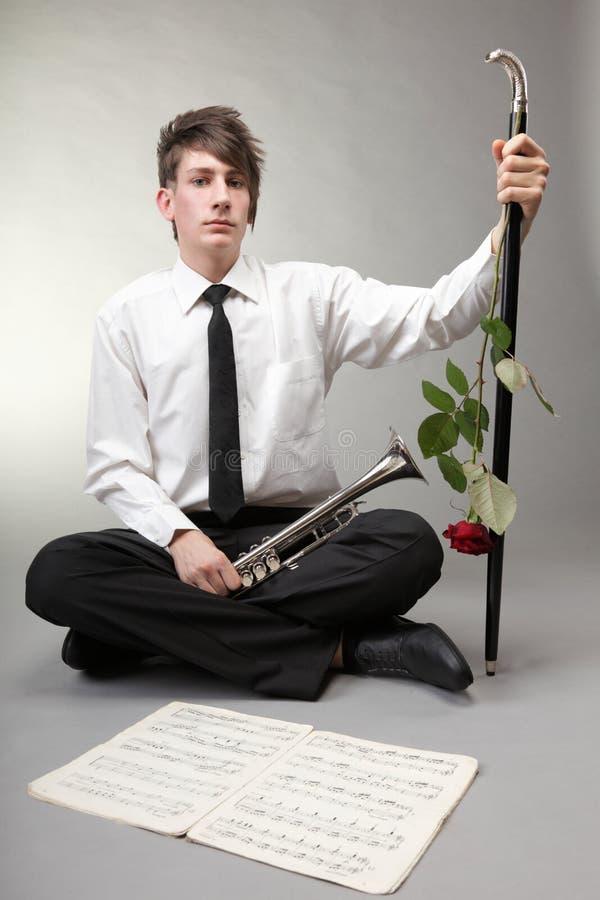 Элегантный мальчик подростка с красной розой и старой трубой. Музыка влюбленности. стоковая фотография rf