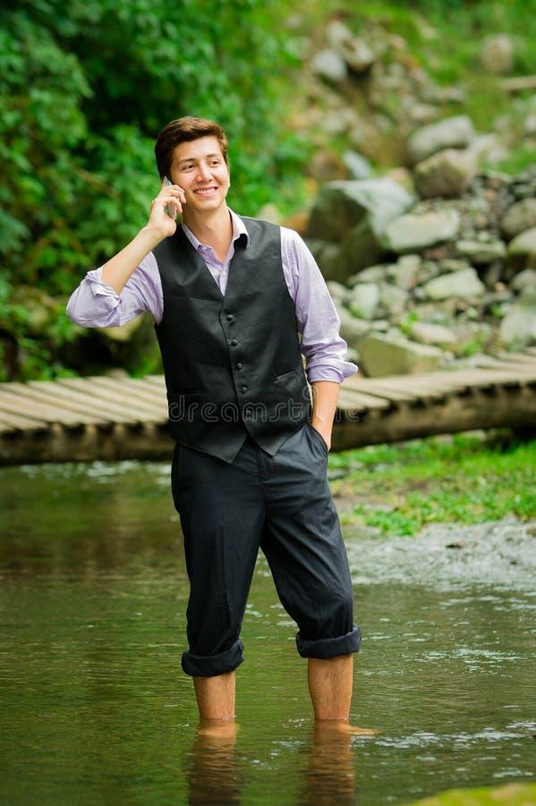 Элегантный молодой человек используя сотовый телефон в озере стоковые фото