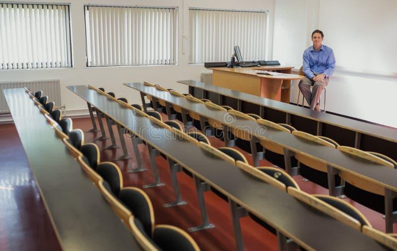 Элегантный мужской учитель сидя в лекционном зале стоковое изображение