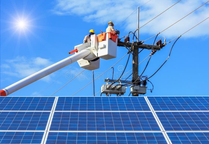 Электрики ремонтируя провод линии электропередач на платформе ведра гидравлической поднимаясь с photovoltaics в станции солнечной стоковые фотографии rf