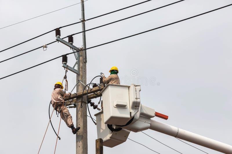 Электрики ремонтируя провод линии электропередач с платформой ведра гидравлической поднимаясь стоковые изображения