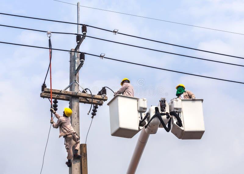 Электрики ремонтируя провод линии электропередач с платформой ведра гидравлической поднимаясь стоковая фотография