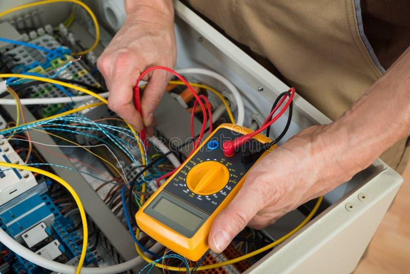 Электрик проверяя коробку взрывателя стоковое фото rf