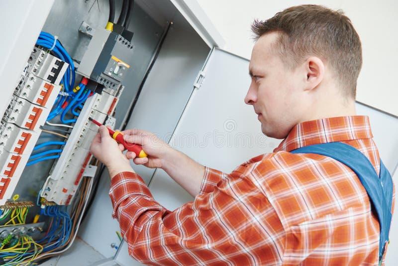 Электрик работает с отверткой в коробке взрывателя стоковое изображение rf