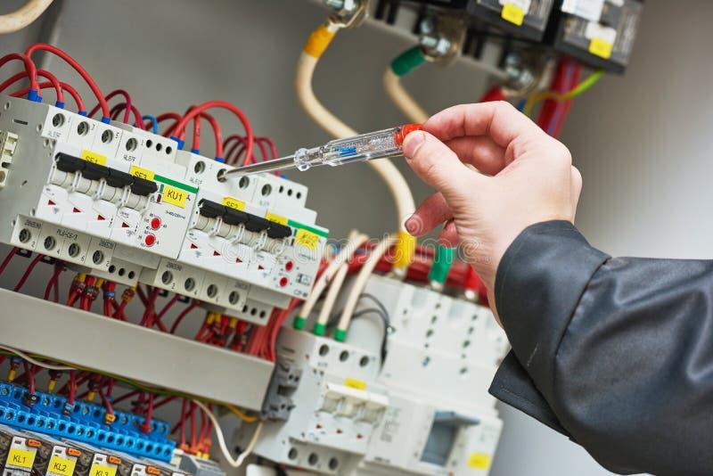 Электрик рассматривая настоящее напряжение тока с тестером отвертки стоковые фотографии rf