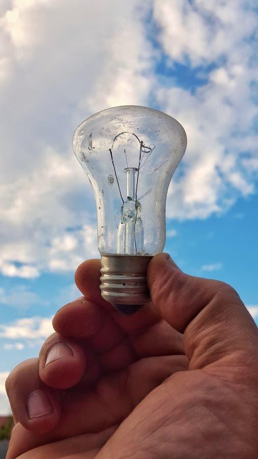 Электрическая лампочка в руке стоковые изображения