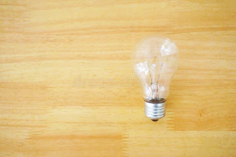 Электрическая лампочка на деревянной предпосылке текстуры стоковые фотографии rf
