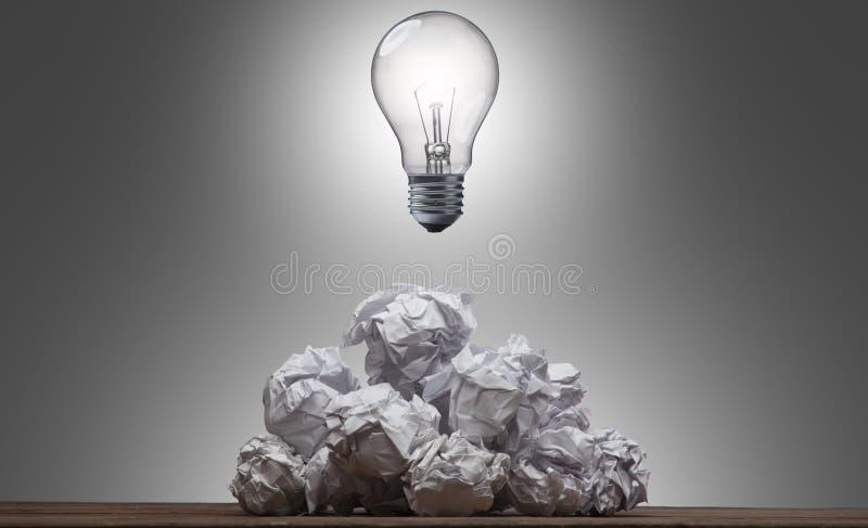 Электрическая лампочка на куче скомканной бумаги стоковая фотография