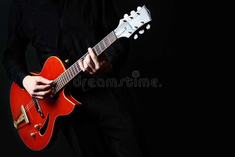 Электрическая гитара с крупным планом рук стоковая фотография