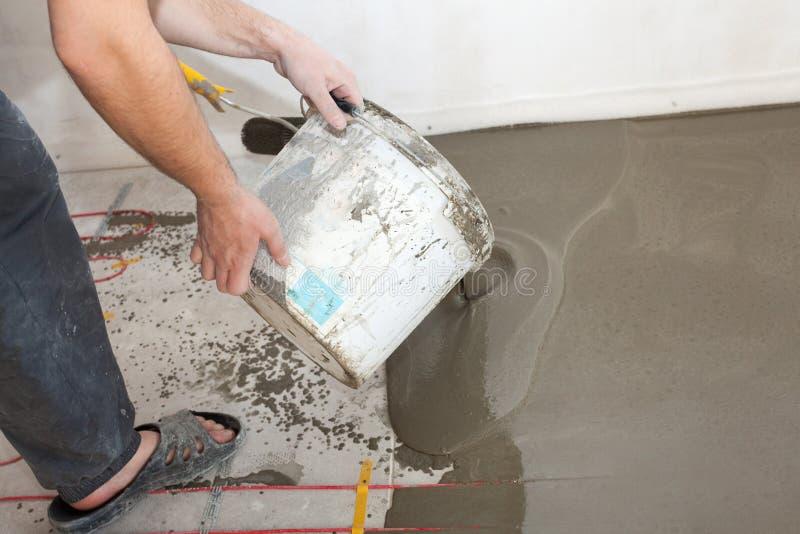 Электрическая установка системы отопления пола в новый дом Бетон работника лить на поле стоковая фотография