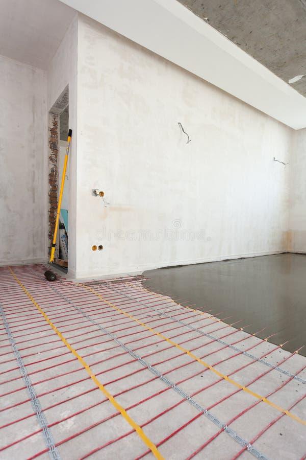 Электрическая установка системы отопления пола в новый дом Комната с белыми стенами, цементом и электрическими проводами стоковые изображения