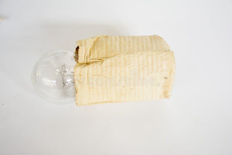 Электрическая электрическая лампочка в бумаге упаковки стоковая фотография rf