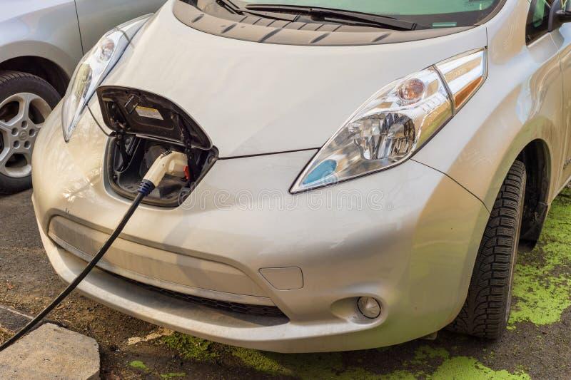 Электрические автомобили поручая на перезаряжать станцию стоковое фото