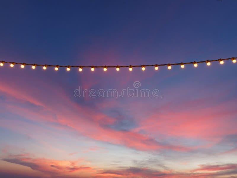 Электрические лампочки на проводе строки против неба захода солнца стоковая фотография