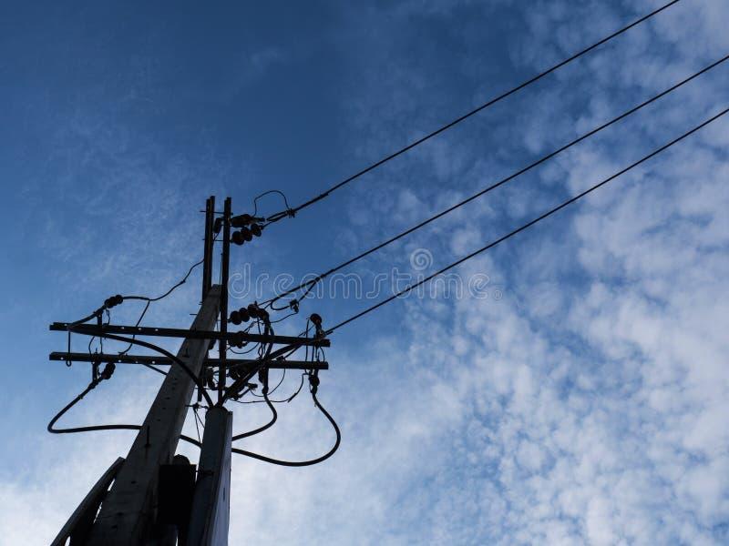 Электрические линии электропередач и провода поляка с голубым небом с лампой стоковое изображение rf