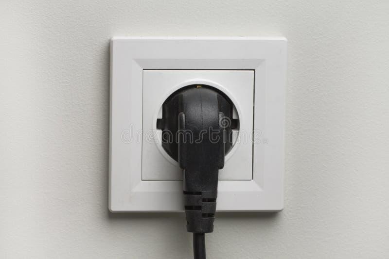 Электрическое белое гнездо и одно заткнули внутри шнур питания на белой предпосылке стены стоковые фотографии rf