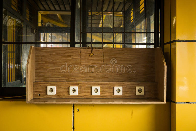 Электрическое гнездо на деревянной стене на поручая объекте в фото публичного места вокзала принятом в Джакарту Индонезию стоковое фото