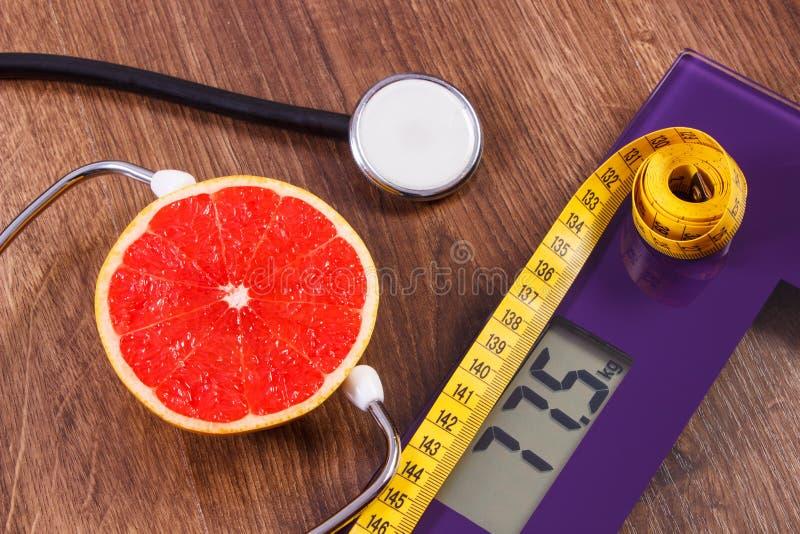 Электронный масштаб ванной комнаты, сантиметр и свежий грейпфрут с стетоскопом, уменьшением и здоровыми образами жизни стоковая фотография