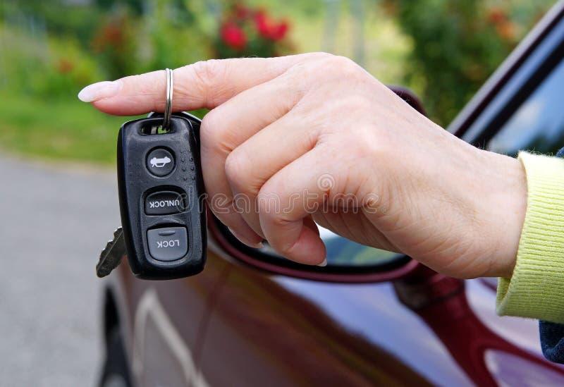 Электронный Remote ключа автомобиля в женской руке стоковое изображение