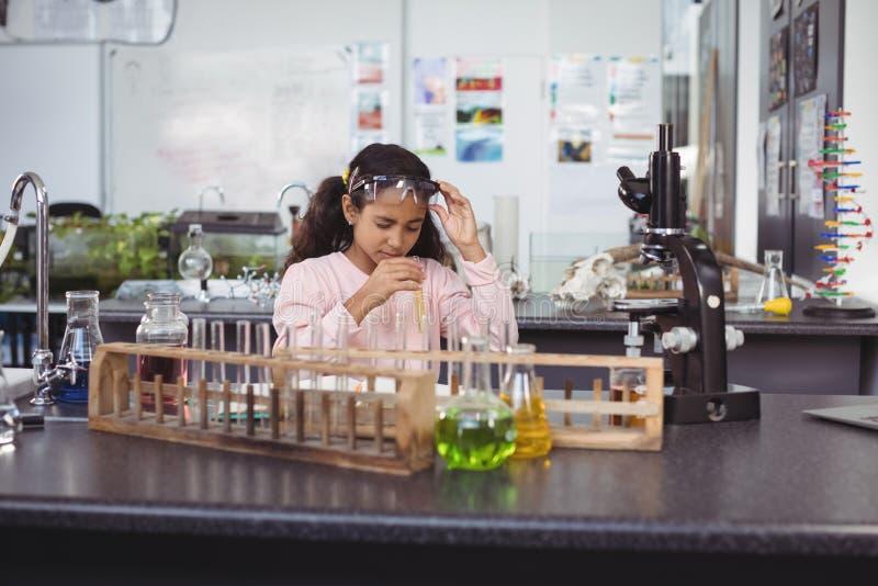 Элементарный студент держа пробирку на лаборатории стоковое фото
