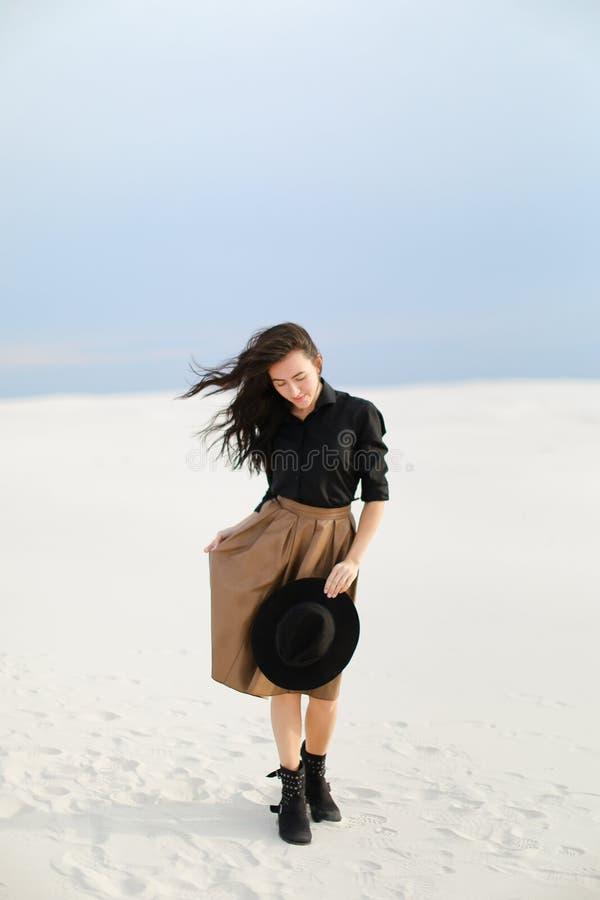Юбка кавказского женского фото модельная нося, черная блузка с шляпой и положение на снеге стоковая фотография