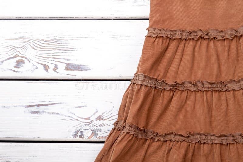 Юбка коричневого цвета Babycord, деревянная предпосылка стоковая фотография