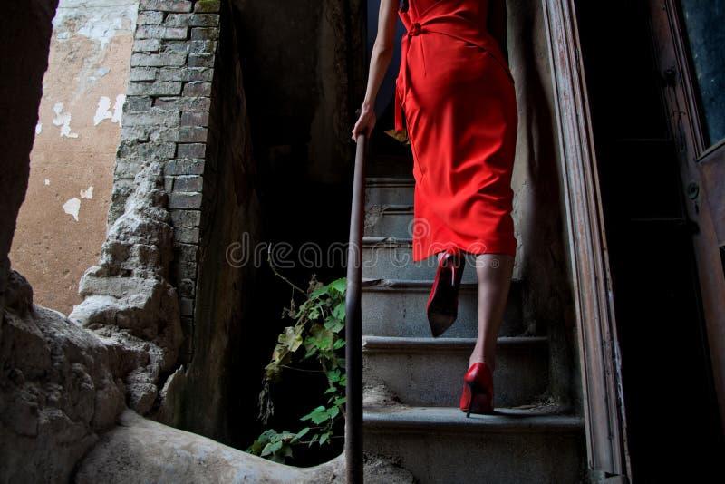 Юбка носки женщины красная и высокие пятки на лестницах в старом доме стоковые фото