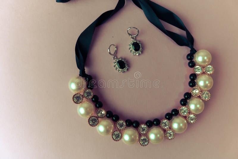 Ювелирные изделия, ожерелье и серьги модных блестящие женщин красивых дорогих драгоценных сияющих ювелирных изделий с жемчугами и стоковые фотографии rf