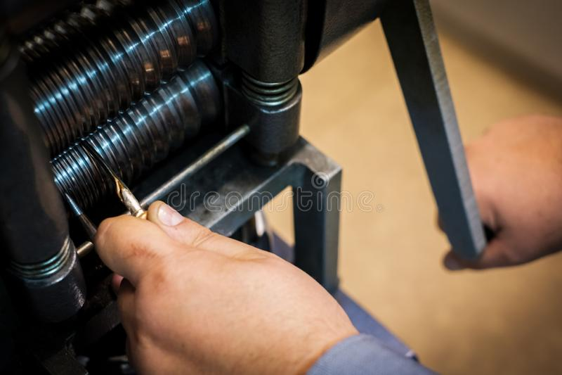 Ювелир формируя серебр или золото части в прессе крена стоковое фото