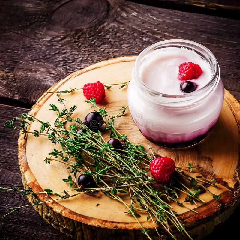 Югурт с ягодами и травами на деревянной предпосылке стоковое изображение rf