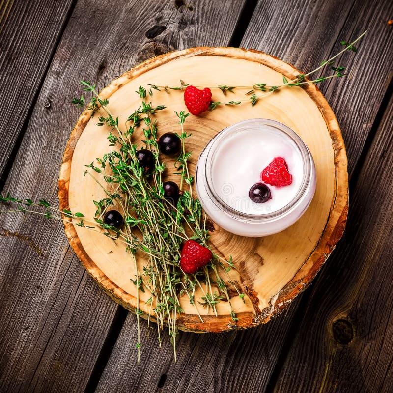 Югурт с ягодами и травами на деревянной предпосылке стоковые фото
