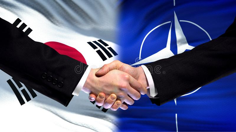 Южная Корея и рукопожатие НАТО, международное приятельство, предпосылка флага стоковое фото rf