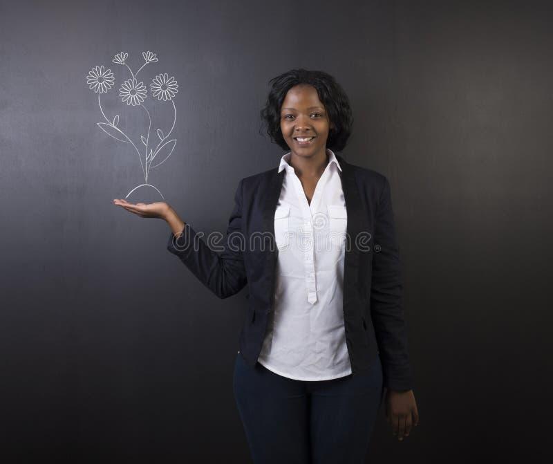 Южно-африканские или Афро-американские учитель или студент женщины против цветков классн классного растущих стоковые фото