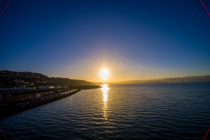 ЮЖНЫЙ ОСТРОВ, НОВАЯ ЗЕЛАНДИЯ 25-ОЕ МАЯ 2017: Красивый заход солнца в horizont, смотря от парома который обеспечивает ежедневно стоковое фото rf