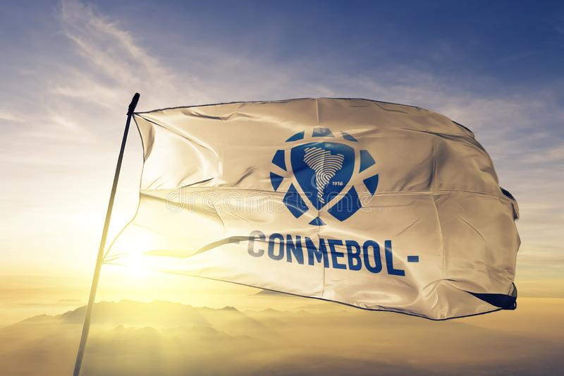Южный - ткань ткани ткани флага конфедерации CONMEBOL американского футбола развевая на верхнем тумане тумана восхода солнца иллюстрация штока