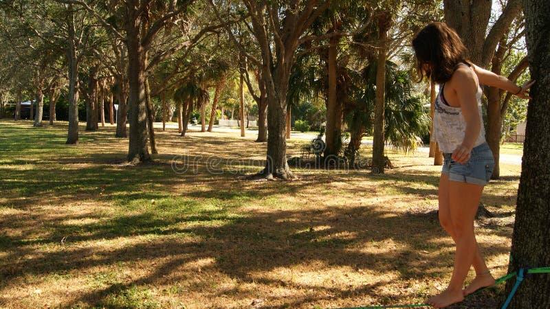 ЮПИТЕР, ФЛОРИДА США - 17-ОЕ ИЮНЯ 2017 Молодая женщина делая практикуя slackline на общественном парке в Флориде стоковое фото rf