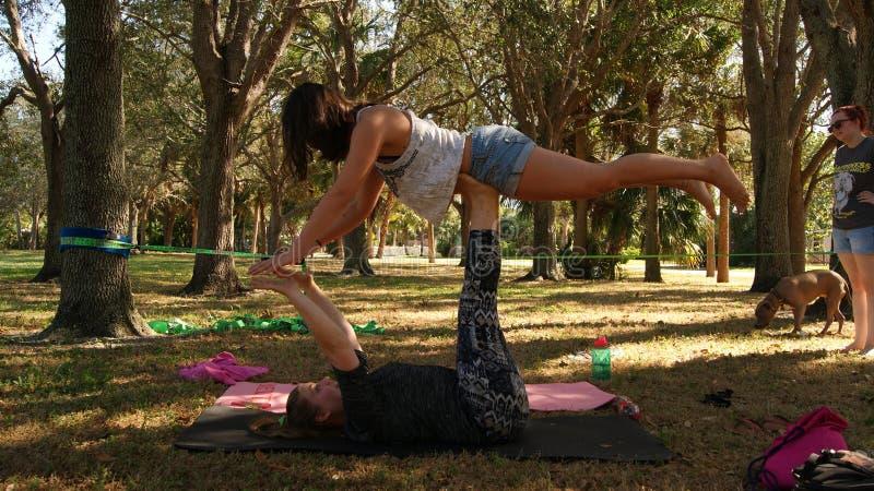 ЮПИТЕР, ФЛОРИДА США - 17-ОЕ ИЮНЯ 2017 Молодые женщины делая йогу & slackline acro на общественном парке в Флориде стоковые изображения rf