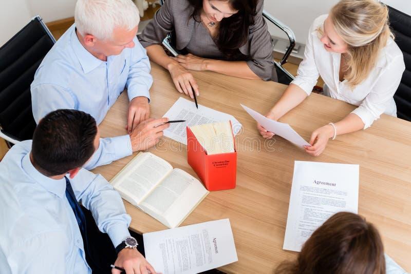 Юристы в документах и согласованиях чтения юридической фирмы стоковые изображения rf