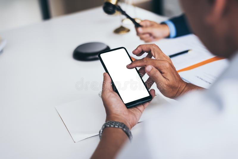 Юристы среднего возраста 2 мужские работая с умным телефоном в офисе с молотком стоковое фото