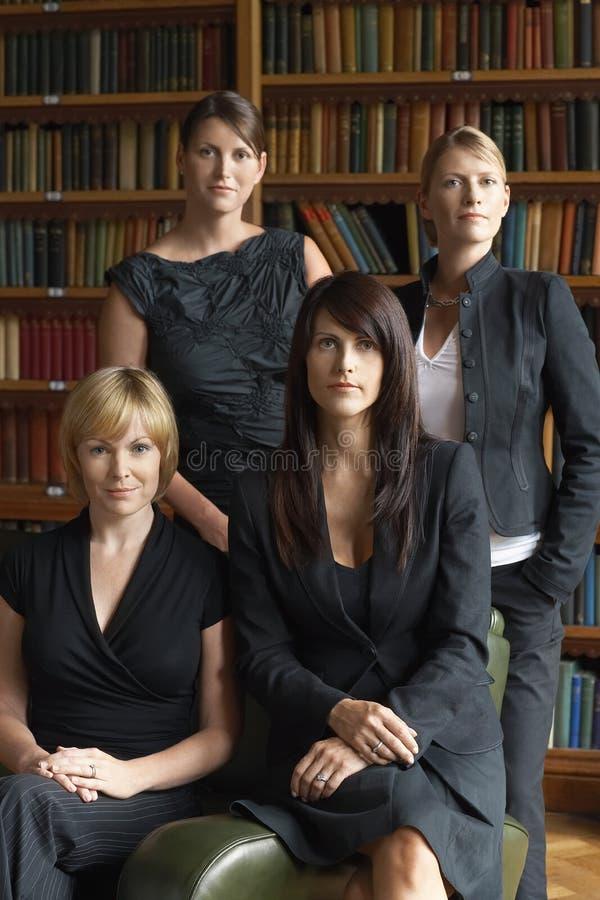 Юристы стоя совместно в библиотеке стоковые фото