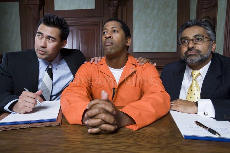 Юристы с преступником в суде стоковые фотографии rf
