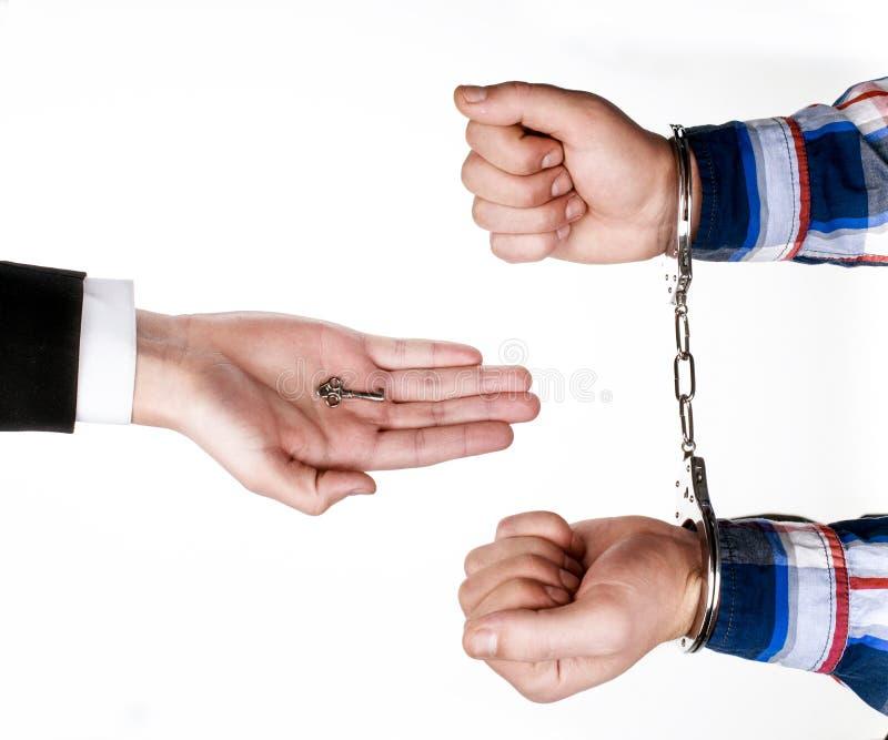 Юрист дает ключ наручников к пленнику стоковые фото