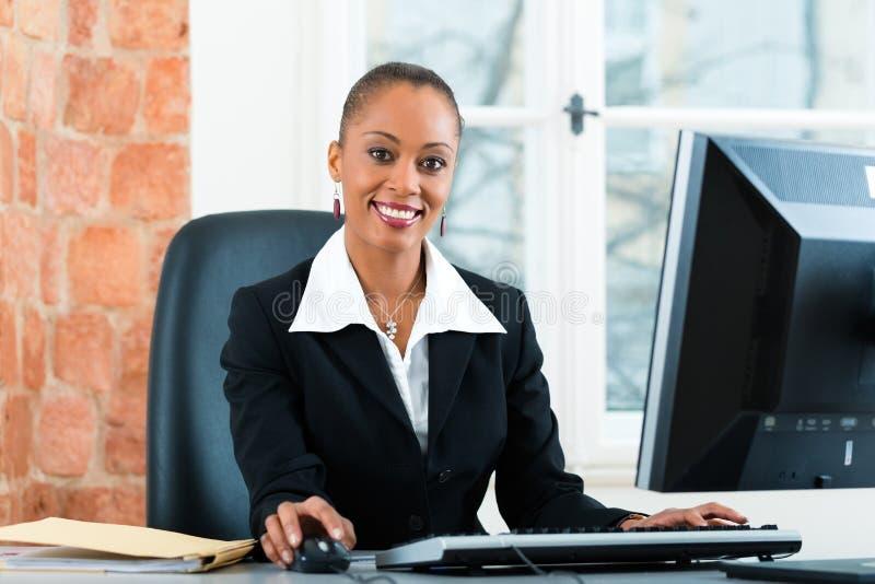 Юрист в офисе сидя на компьютере стоковое фото