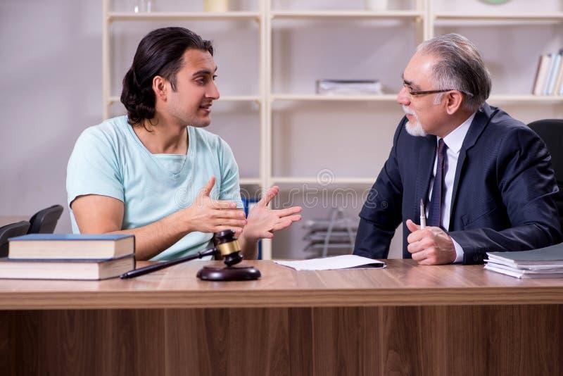 Юрист молодого человека посещая опытный мужской стоковое фото