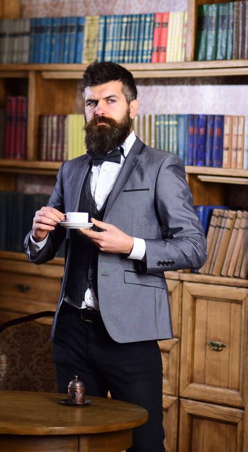 Юрист стоит в роскошном интерьере с чашкой чаю или кофе стоковая фотография
